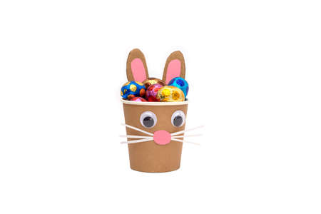 Bunny craft paper cup isolated on white, chocolate eggs in foil, holiday activity for kids