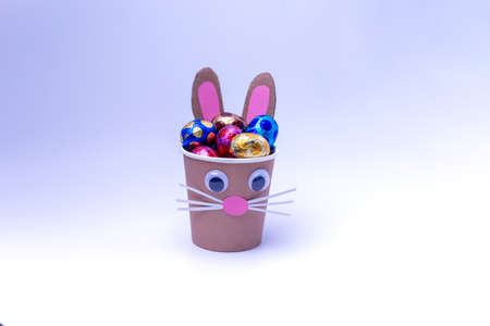 bunny craft from a paper cup filled with chocolate eggs in foil, holiday activity for kids Фото со стока