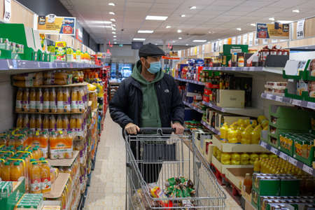 Angers, Maine et Loire, France - December 10 2020: grocery shopping, man wearing mask buying food in supermarket
