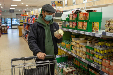 Angers, Maine et Loire, France - December 10 2020: man standing in grocery shop with can, person wearing mask in supermarket