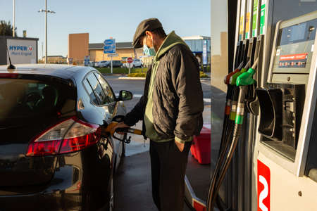 Angers, Maine and Loire, France - December 10, 2020: masked man at the gas station refueling the car with gasoline