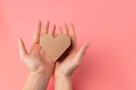 abstract heart in hands, craft paper present, top view, pink background