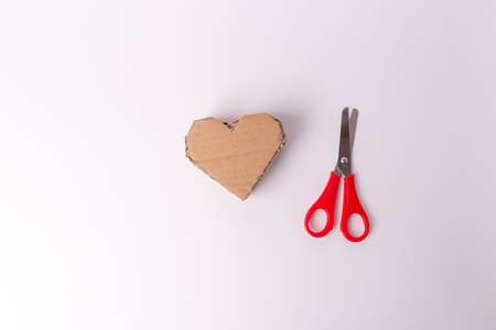recycled cardboard heart shape craft, red scissors on white background
