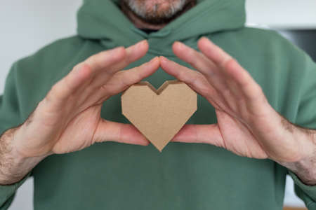 soft focus on hands hold abstract love symbol, heart shape object made of recycled cardboard paper