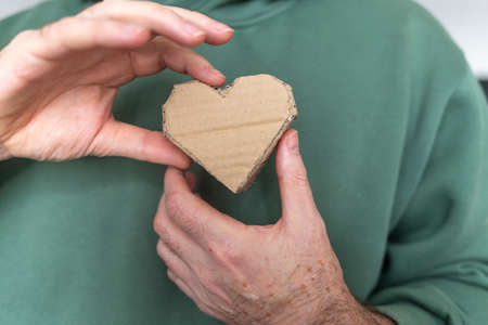raw paper heart shape object craft in hands,