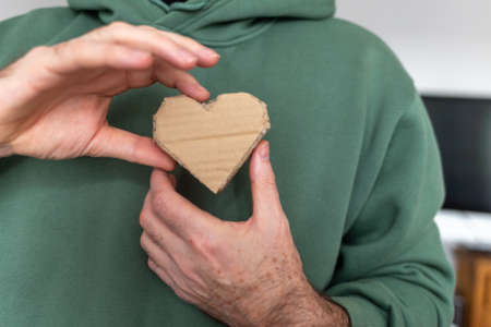 Abstract love symbol in mans hands, shape heart craft made of recycled cardboard paper, green background Фото со стока