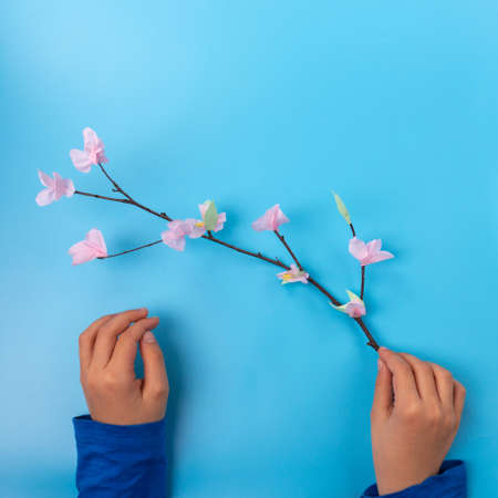 kids holds an easy easter tree branch with flowers, spring craft for kids, Фото со стока