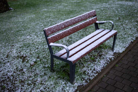 Realistic bench with snow, cold weather, frozen green grass