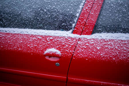 Closeup of a red car covered in snow, Side of a frozen car in a cold winter morning