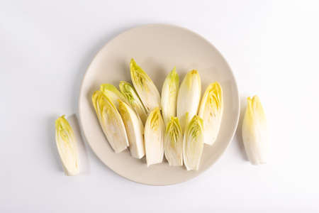 endive on plate top view on white background, salad chicory roots, healthy organic food concept, vegetarian