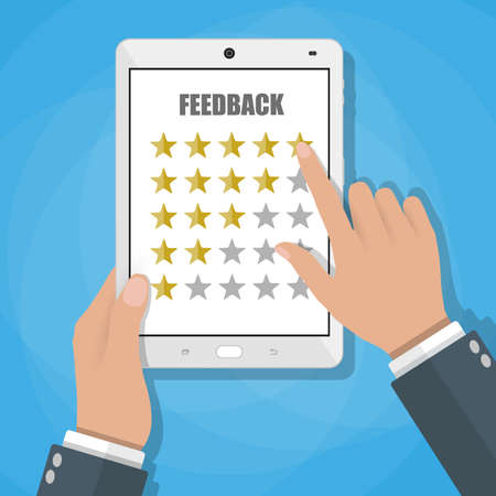 fife: Hand holding and pointing ttablet touch screen with fife rate stars. Feedback form, Customer service. online review feedback concept.
