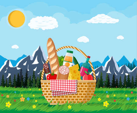WIcker cesta de picnic llena de productos y la naturaleza Foto de archivo - 79939235