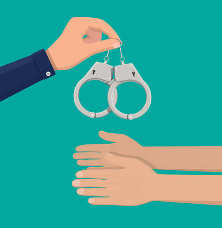 Metal handcuffs in hand of police officer