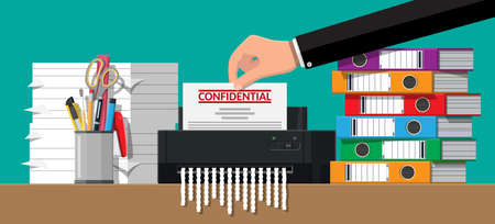 Hand putting document paper in shredder machine.