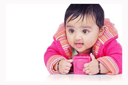 facing the camera: baby holding pink block facing camera