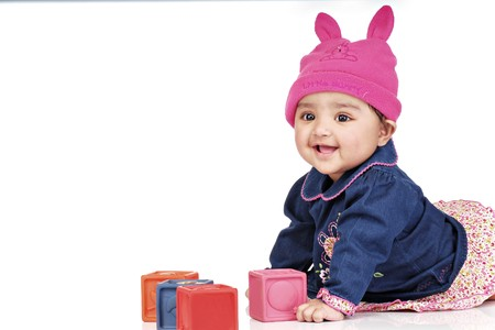 indian blue: smiling baby girl playing with blocks lying on floor