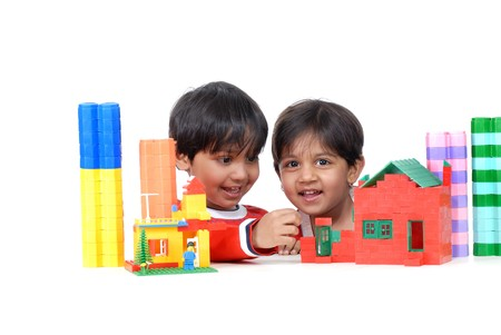twin house: brother and sister making house with colorful blocks