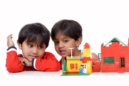 kindergarten toys: brother and sister observing houses of blocks