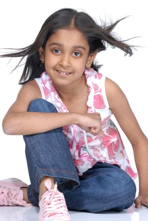 little girl sitting: cute girl posing over white background