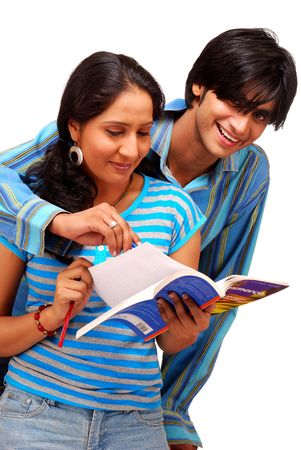 college boy and girl scrolling pages of text book  photo