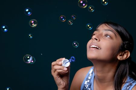 Cute girl having fun with lots of bubbles
