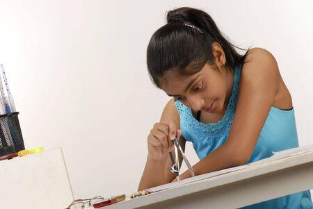 writing activity: school girl using compass to study geometry  Stock Photo