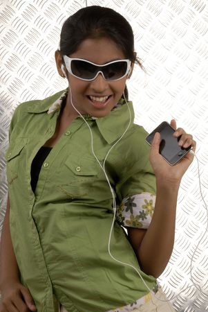 portable mp3 player: beautiful girl listening music on her portable mp3 player wearing sunglasses