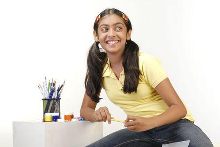 cheerful school girl holding yellow color pencil Standard-Bild
