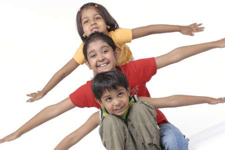 convivencia familiar: tres ni�os sentados con los brazos hacia el exterior Foto de archivo