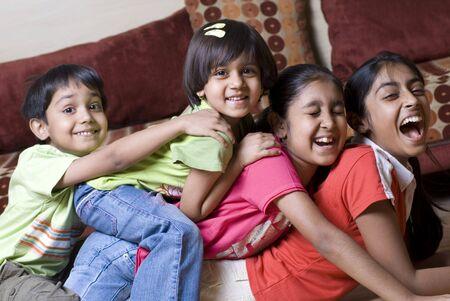 familia unida: hermanos de edades comprendidas entre los once a cuatro se divierten juntos en casa
