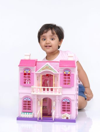 doll house: 2-3 years old baby girl sitting behind the doll house
