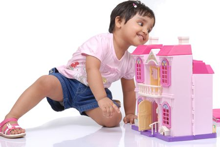doll house: 2-3 years old baby girl looking behind the doll house  Stock Photo