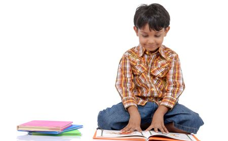 Young boy sitting on the floor reading a book against a white background