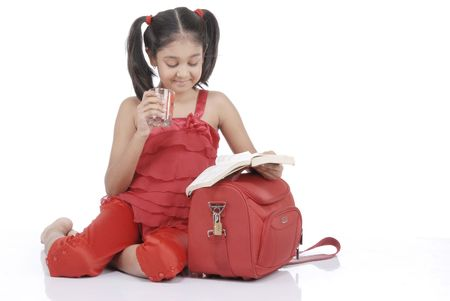 little girl drinking water and reading book over white background  photo
