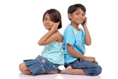 Twins brother and sister on mobile sitting with backs to eachother  Banco de Imagens