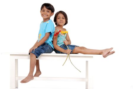 Sister holding two flowers sitting backs to brother on bench