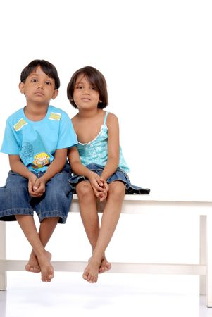little boy and girl: Cute twins sitting on bench over white background  Stock Photo