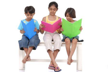 ninos indios: hermano y dos hermanas de la lectura de libros interesantes sentado en el banquillo Foto de archivo