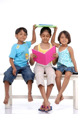 Twins brother and sister putting books on elder sisters head  photo