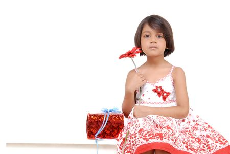 little girl holding red flower sitting with present wrapped in red paper   photo