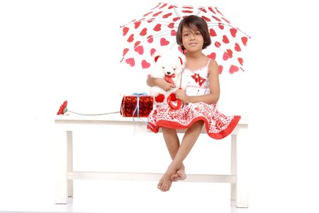 little girl wearing red dress holding umbrella and giving protection to teddy bear and objects  photo