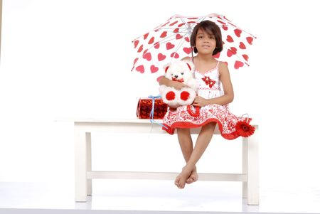 fashionable little girl wearing red dress holding umbrella and sitting with red objects Stock Photo - 5592951