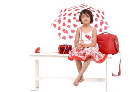 fashionable little girl wearing red dress holding umbrella and sitting with red objects  photo