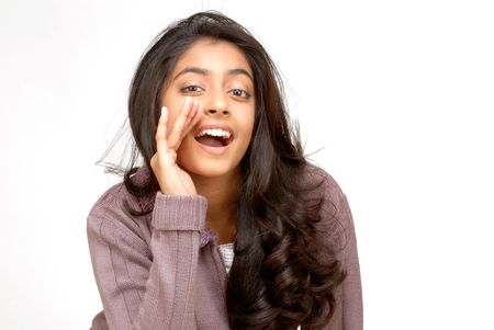 beautiful indian girl face: beautiful teenager girl whispering secrets into camera  Stock Photo