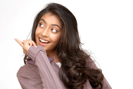 indian teenager girl pointing at copyspace