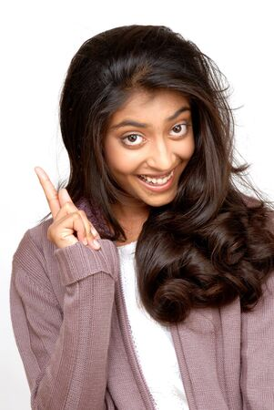 beautiful indian girl pointing on white background  photo