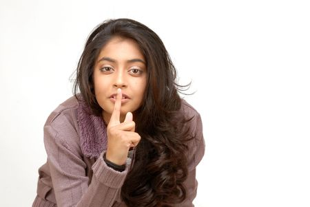 portrait of indian girl with finger on lips photo