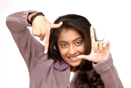 making face: indian girl making a framing her face with her hands