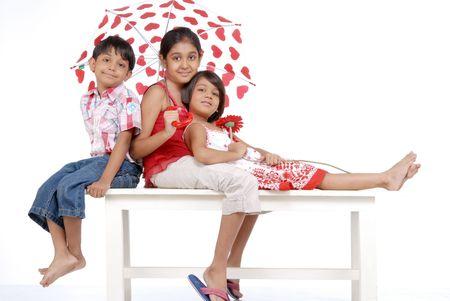 elder sister covering loving twins in umbrella