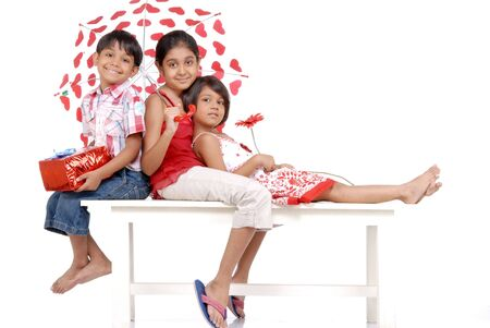 protect family: elder sister covering loving twins in umbrella